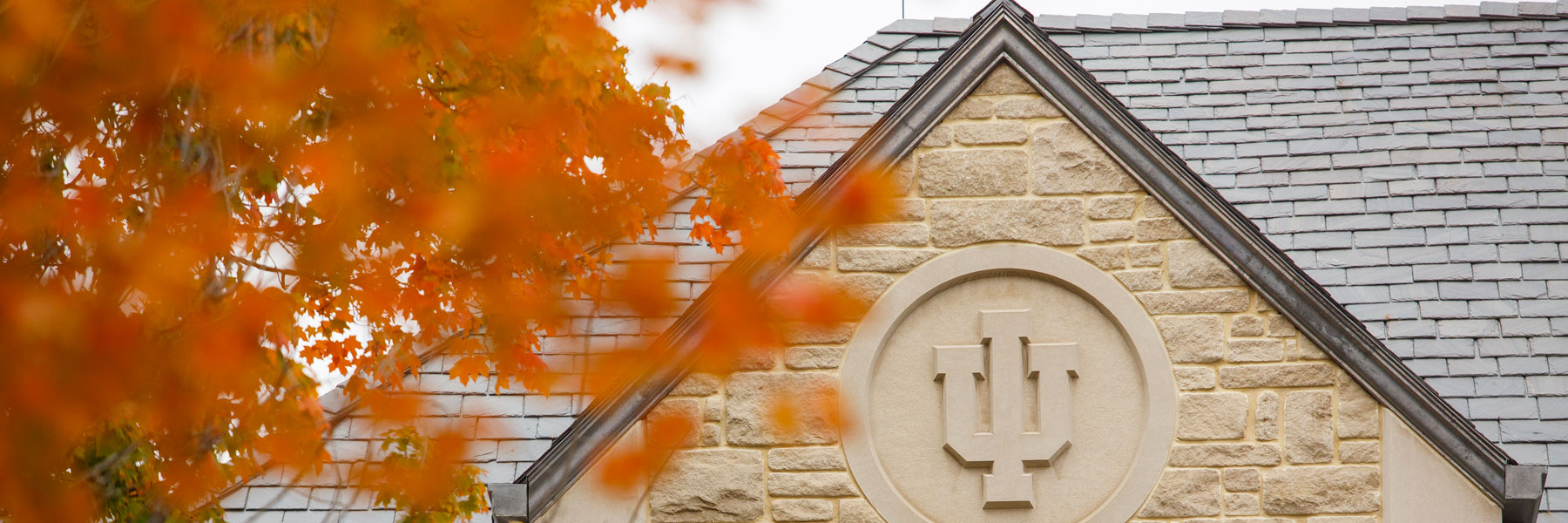 The IU trident on a campus building surrounded by Fall leaves