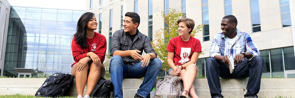A group of four students meet outside a campus building