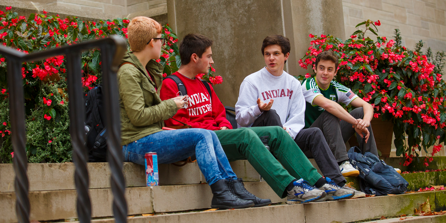 Students talk with a student mentor on the steps of a building.